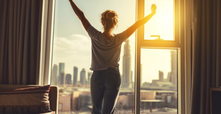 happy woman stretches and  opens curtains at window in morning