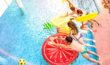 Top view of active friends jumping at swimming pool party – Vacation concept with happy guys and girls having fun in summer day at luxury resort – Dynamic young people on warm bright sunshine filter