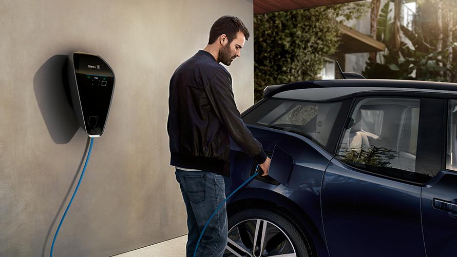 Homem carregando carro elétrico.