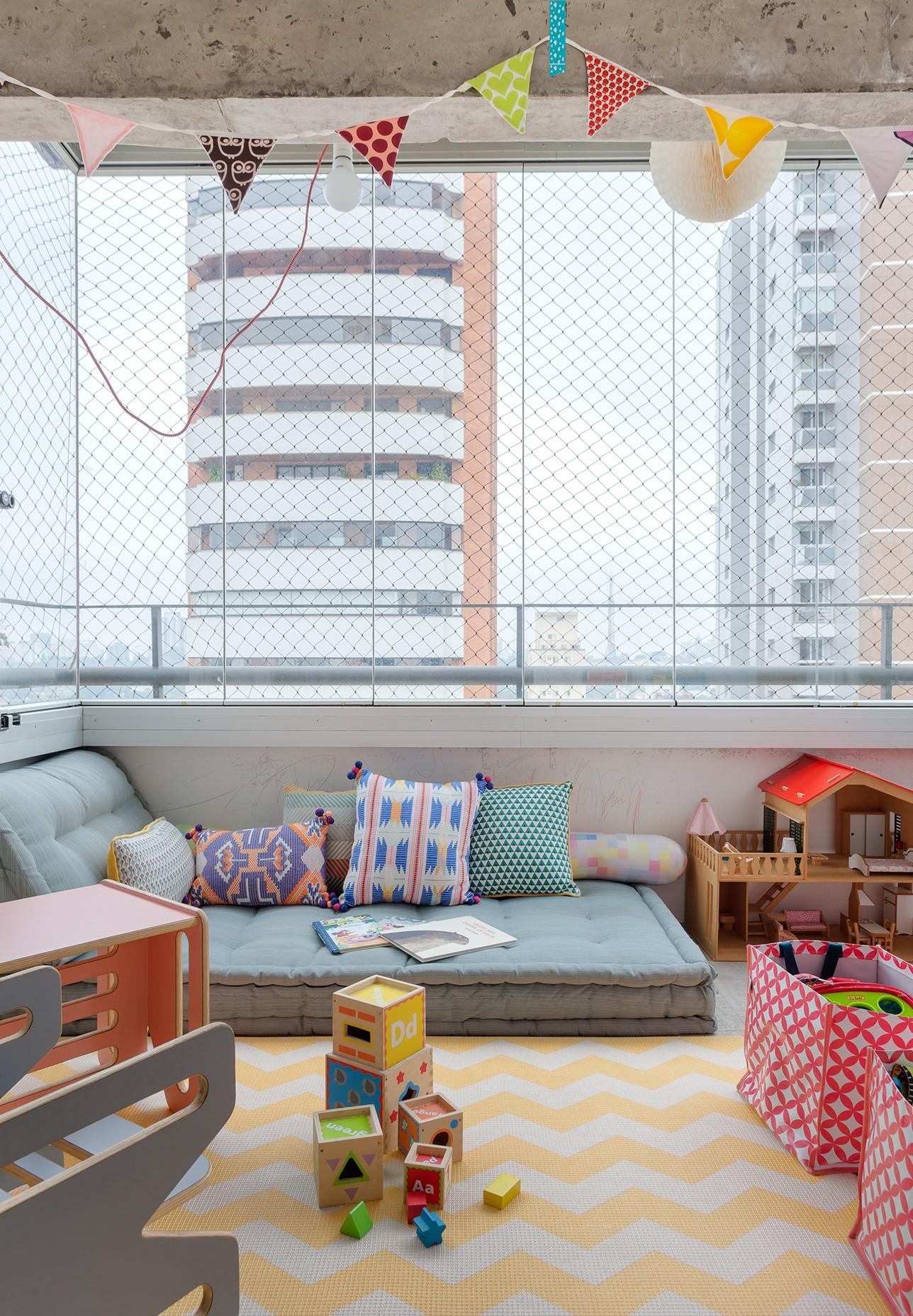 Área com espaço para as crianças com brinquedos e decoração infantil.