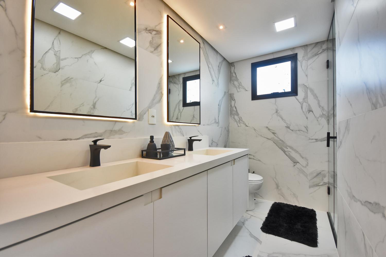 Banheiro da maior suíte do apartamento decorado do Residencial Piemonte. Os espelhos, metais pretos e revestimentos marmorizados podem ser adquiridos pelos projetos de personalização.