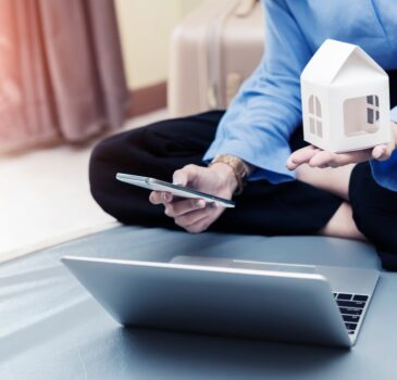 loan-planing-for-new-home-concept-businesswoman-holding-home-model-and-mobile-with-laptop-on-bed-at_t20_vKznWv (1)