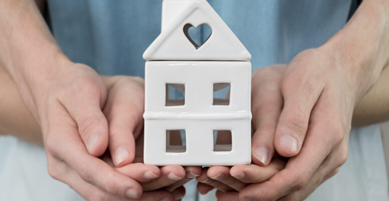 young-family-is-holding-toy-house-in-hands-cozy-man-people-home-finance-property-buy-sale-concept_t20_a8kKEx